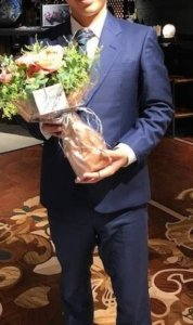 花を持つスーツ男性